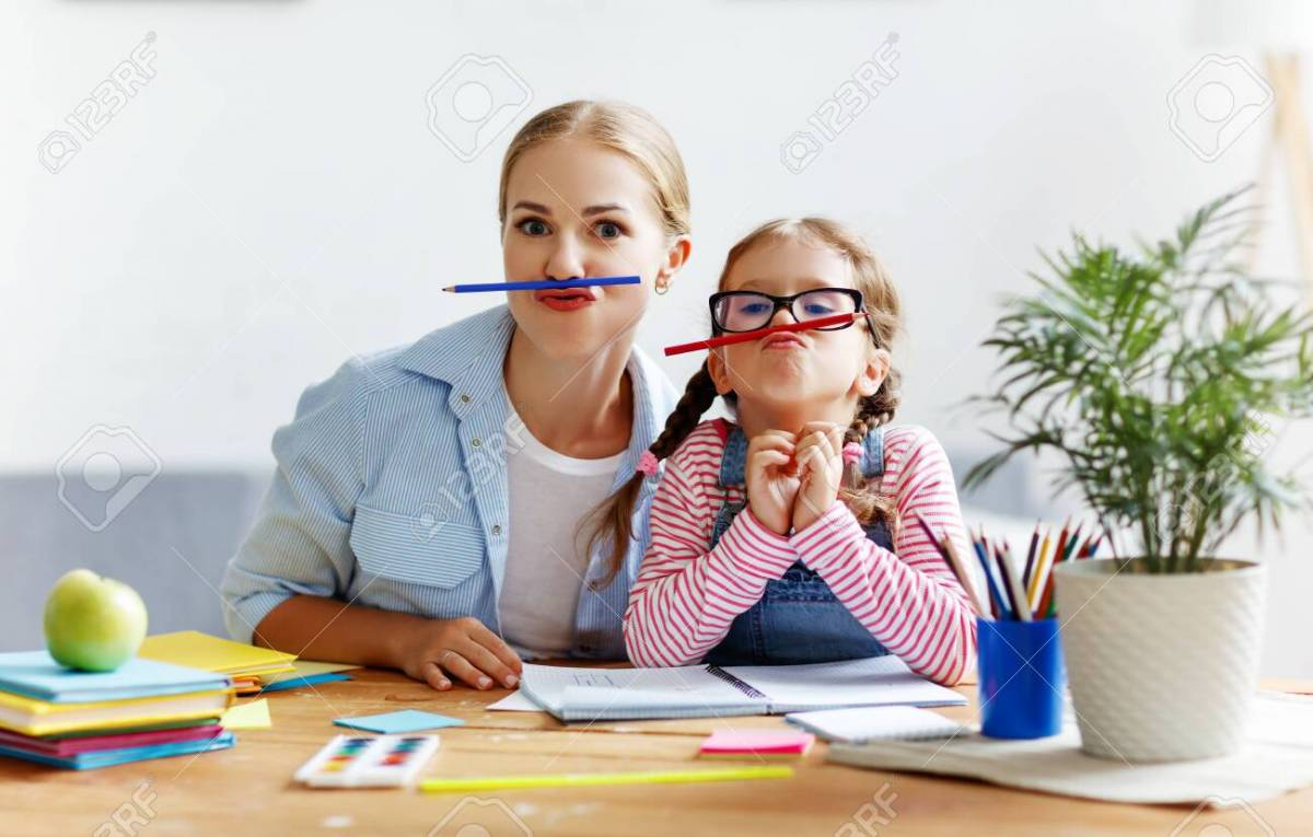 127877152 funny mother and child daughter doing homework writing and reading at home